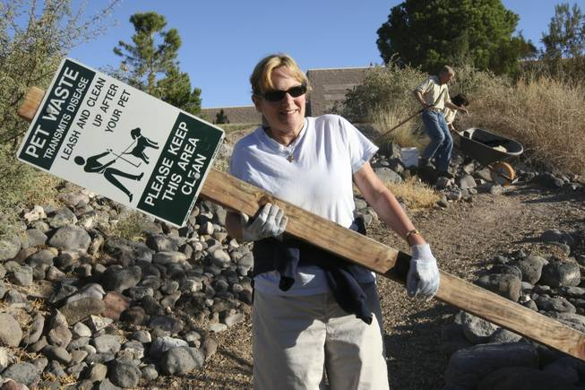 Pastor Marta Poling-Goldenne of New Song Church carries a sign Saturday to be placed along the trails of the Pittman Wash behind Silver Springs Recreation Center for Project Green Volunteer Make A Difference Day.