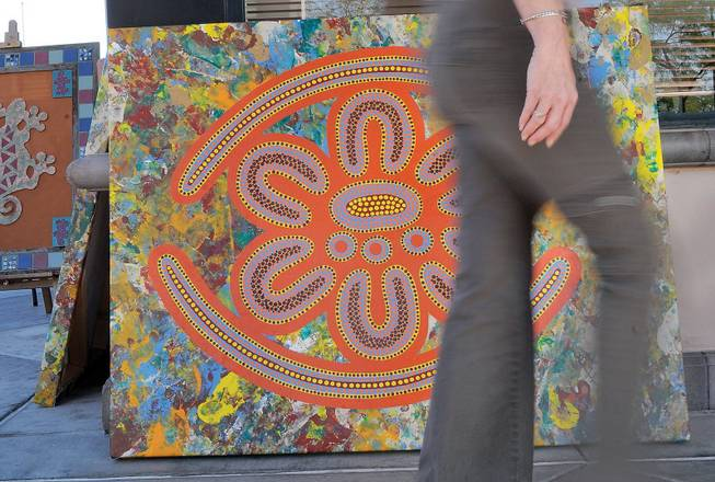 An art browser strolls past mosaic wall art by Hal Carter during the second day of the Art Walk at Trails Village Center.