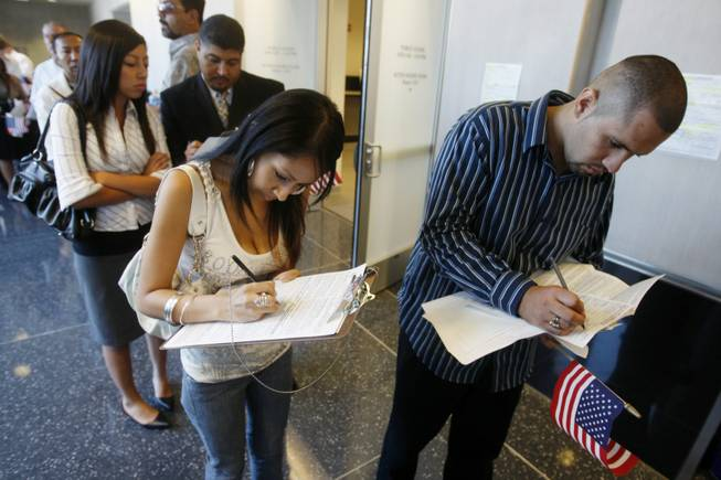 New U.S. citizens Jenette Chavez, 18, and Josue Cano, 20, fill out voter registration forms in August at the Lloyd D. George federal courthouse in Las Vegas in 2008.