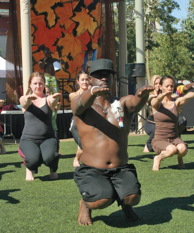 George McLaurin, center, who has used bikram yoga to help survive a kidney transplant, leads the bikram yoga demonstration during the annual Bishnu Ghosh Yoga competition at Town Square Park.