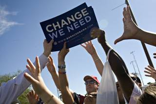 Campaign signs are handed out at an Obama rally where Michelle Obama spoke on the Cheyenne campus of the College of Southern Nevada in North Las Vegas on Monday.