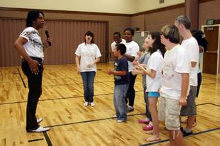 Popular singer Phil Flowers, left, instructs the students of Life Long Dreams during rehearsals at the Church of Jesus Christ of Latter-day Saints gym.