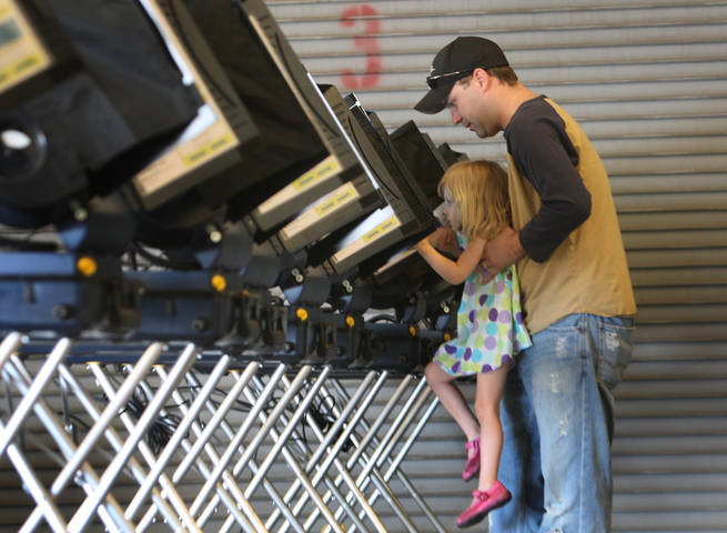 Wendy Davison, 2, helps her father Jeremy Davison cast his ballot at Fire Station #3 in Henderson