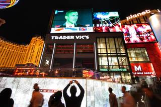 A man takes a photo as pedestrians on the Las Vegas Strip stop outside the Planet Hollywood to watch television news coverage of Democratic President-Elect Barack Obama giving his acceptance speech Tuesday night.