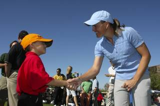 Excited to meet a professional golfer, volunteer Matthew Manganello, 7, shakes the hand of LPGA player Stephanie Louden during the Danny Gans' Partee Fore Kids Celebrity Pro-Am at DragonRidge Country Club on Monday.