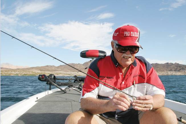 Local angler Mike Sisco hooks grub bait to his fishing line as he prepares to fish Sunday at Lake Mead.