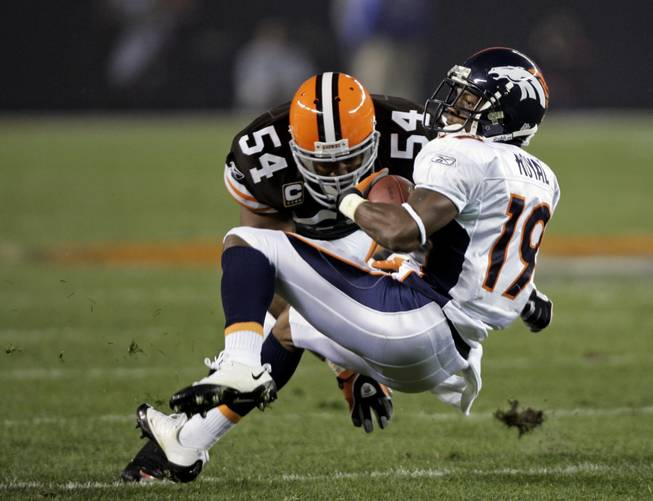 Denver Broncos wide receiver Eddie Royal (19) is tackled by Cleveland Browns linebacker Andra Davis (54) during an NFL football game Thursday, Nov. 6, 2008, in Cleveland.