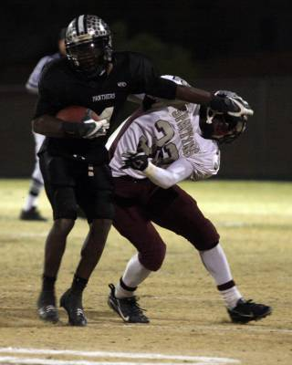Palo Verde running back Sidney Hodge stiff-arms Cimarron-Memorial defensive back Roderick Washington during the Sunset Regional football semifinals at Palo Verde High School on Friday.