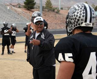 Palo Verde senior captain Dave Castro (45) listens to instructions from his father and defensive coordinator Dave Sr. during Tuesday's practice.