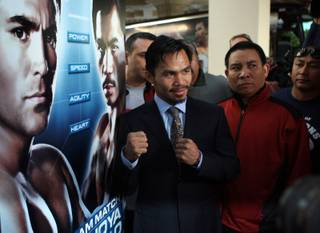 Manny Pacquiao poses by a sign promoting his welterweight fight with Oscar De La Hoya as he makes his official