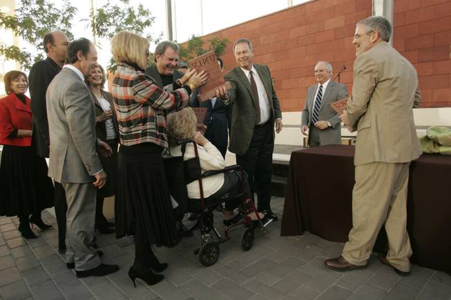 Sun Editor Brian Greenspun, joined by family, hands off a commemorative sculpture with the help of UNLV President David Ashley, second from right, and Lee Bernick, right, interim dean of the Greenspun College of Urban Affairs, which will be housed in the new hall.