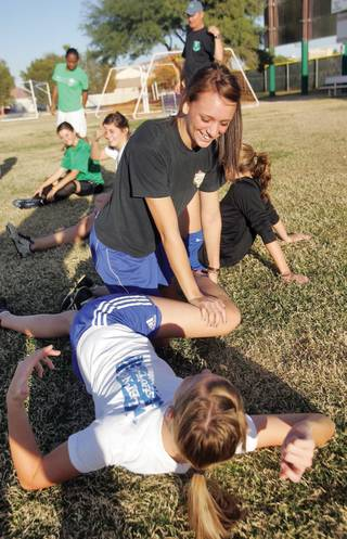 Kayla Varner helps her teammate, Megan Brickley, stretch out at the beginning of soccer practice at Green Valley High School.