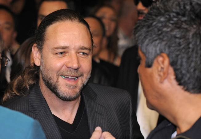 Actor Russell Crowe, left, greets comedian George Lopez prior to Oscar De La Hoya's welterweight boxing match against WBC lightweight champion Manny Pacquiao in Las Vegas on Saturday, Dec. 6, 2008.
