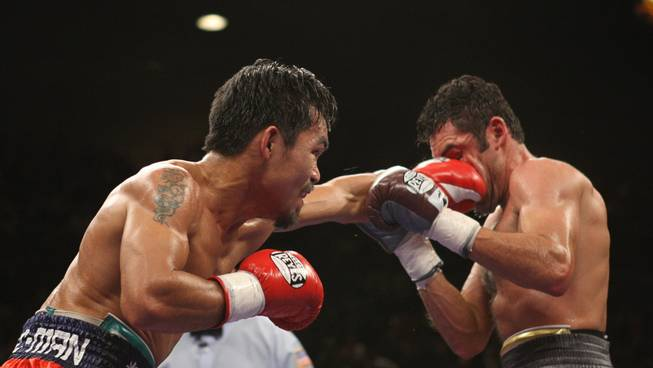 Manny Pacquiao of Philippines connects with Oscar De La Hoya of the U.S during their 'Dream Match' at the MGM Grand Garden Arena.
