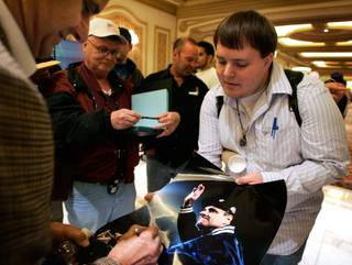 Mark Sherfey, a student from Bowling Green, Kentucky gets an autograph from Joe Torre during the Major League Baseball Winter Meetings at the Bellagio.