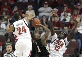 Rene Rougeau and Brice Mussamba play defense on Demerius Ward of Western Michigan at the Orleans Arena, where UNLV took on Western Michigan on Sunday afternoon. UNLV won 70-61.