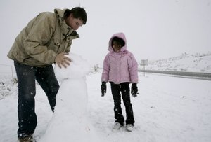 Alexis Winston, 5, and Ryan Cuevas build a snowman on the side of the road near Red Rock Canyon on Monday.