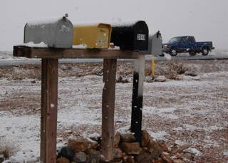 Mail boxes sit covered with snow along Blue Diamond Road Monday morning.