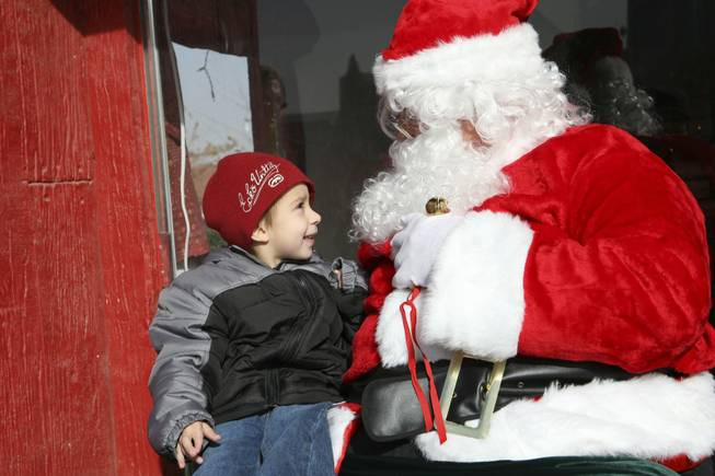 While sitting on Santa Claus' knee at WinterFest, Daniel Stabolito, 3, asks for Wall-E the robot during the 2008 WinterFest Saturday at the Henderson Events Plaza.