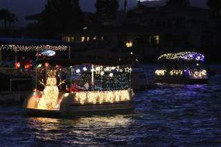 Electric boats decorated with twinkling lights and holiday themes cruise the choppy waters along the shoreline at The Lakes Town Center Plaza during the annual Electric Light Boat Parade Saturday.