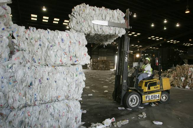A pile of recyclables is fed into a conveyor belt to be sorted at the Republic Services recycling facility in April.