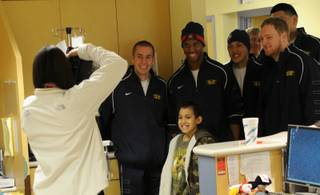 Members of the BYU and Arizona football teams visit Sunrise Children's Hospital to deliver gifts to long-term patients.
