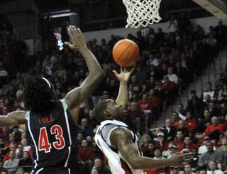 Wink Adams lays it up and over Arizona's Jordan Hill on Saturday at the Thomas & Mack Center.