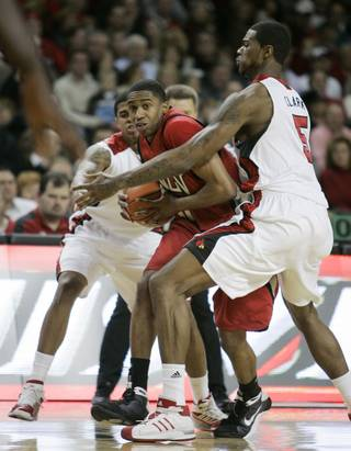 UNLV's Oscar Bellfield looks for help as he is trapped between Louisville defenders Edgar Sosa, left, and Earl Clark during the first half.