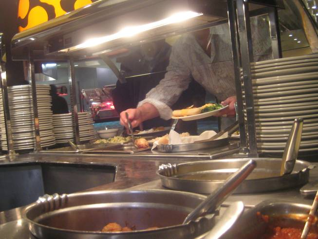 <p>8:05 p.m.: Hungry revelers served (themselves) up plates of prime party-fueling fare and got their fill of New Year's Eve eats at the Palms' Bistro Buffet.</p>