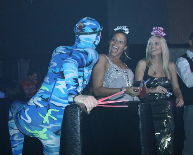 <p>12:30 a.m.: A pair of partiers is surprised by a Perfecto performer at Rain on New Year's Eve.</p>