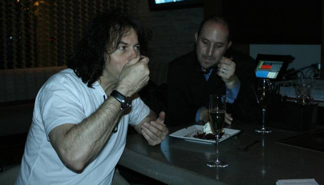 <p>1 a.m.: Chef Kerry Simon, left, enjoys a glass of champagne and shares some chocolate-peppermint mousse cake with the director of public relations for Palms Hotel and Casino, Larry Fink, after a hectic New Year's Eve at his namesake restaurant at Palms Place, Simon.</p>