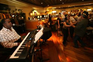 Lounge musician Bobby D. performs for a dancing crowd during New Year's Eve festivities at the Round Bar inside the JW Marriott Resort in Summerlin Wednesday, Dec. 31, 2008.