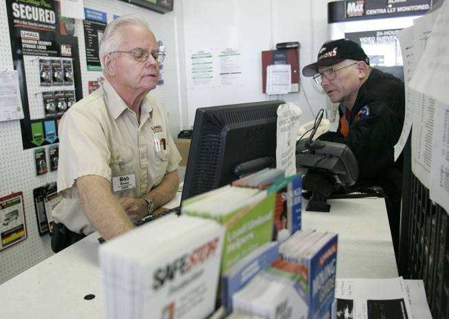 Bob Bower, left, checks on a truck at the U-Haul store Friday for Larry Rhodes, an airplane mechanic who says he's being transferred because travel is down.