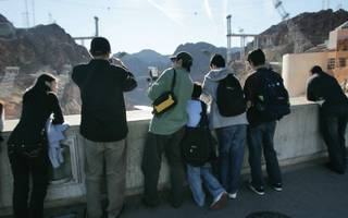 Tourist take photographs from the top of Hoover Dam.
