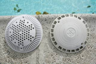 An old pool drain cover, right, is seen next to a new anti-entrapment pool drain covers designed to prevent death. The law requires that all pools and spas to have drain covers installed and a second anti-entrapment system added when there is only a single main drain.