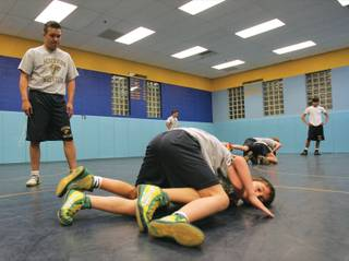 Henderson Youth Wrestling coach Tony Medina, left, looks on as Brady Bransum, 9, and Cole Cauley, 7, bottom, spar during a practice at the Foothill High school wrestling room.