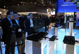 Show-goers look over ultra-thin OLED televisions at a Samsung booth at CES Thursday in Las Vegas.  Samsung unveiled OLED television prototypes with screens ranging from 14 to 31 inches.