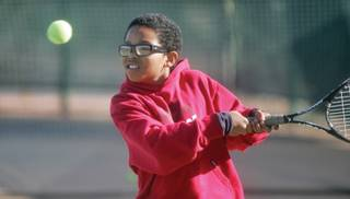 Eli Deville, 11, braces himself to connect with the ball during his tennis lesson at All American Sports Park. The nephew of tennis professionals, Venus and Serena Williams, Deville has picked up the sport quickly since he started playing a little over two months ago.