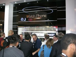 A mad throng -- mad, I tell you! -- cranes for a look at the Touch Watch Phone.