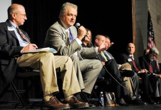 Assemblyman Joe Hardy, left, looks on as Clark County Commissioner Steve Sisolak responds to a suggestion by a member of the audience regarding generating new sources of income for the school district during tough economic times at a town hall meeting Thursday inside the Boulder City High School auditorium.