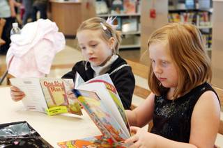 Taylor Simmons, 7, left and Chloe Atwell, 7 read books Saturday at the opening of the Centennial Hills Library.