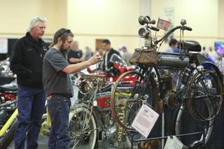 While Craig Murray watches, Terry Cutler takes a photograph of a rare 1907 Yale-California motorcycle Friday during the Las Vegas Antique Motorcycle Auction at the South Point Events Center.  This motorcycle with original paint was originally purchased by a mailman and used to deliver mail.