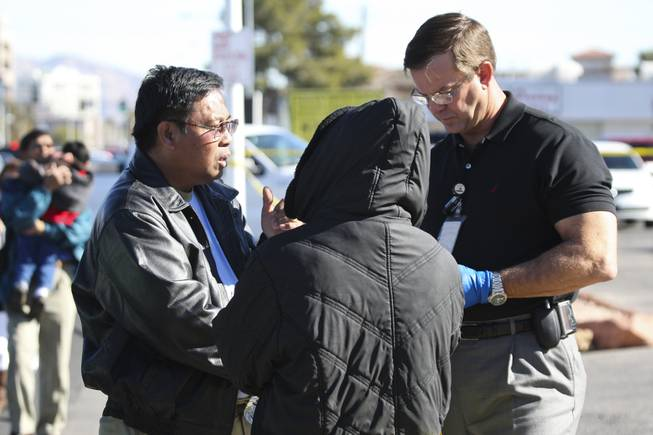 Metropolitan Police Officer Clifford Mogg, right, speaks with potential witnesses in the death of Dr. Edna Makabenta on Monday. The two being interviewed had been parked in front of the doctor's West Charleston office, where a police said a patient killed the doctor then killed himself.
