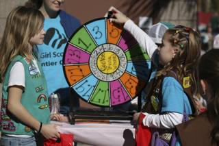 Confident in her cookie knowledge, Jayalyn Buckner, right, turns the cookie trivia wheel after receiving instructions from Nicole Taylor at Henderson Troop 70's booth at the Girl Scouts Cookie Kickoff Carnival Saturday at the Girl Scouts Frontier Council's Training and Service Center.