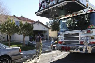 Henderson firefighter Scott Dakus gathers water hoses after helping to extinguish a fire at 507 Chandler Street in Henderson Thursday.