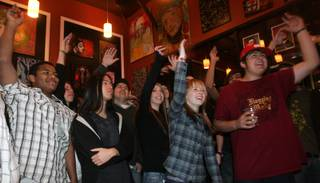 Spectators wave their hands to the music of Dyslexic Duo at Canvas Cafe, 430 E. Silverado Ranch Blvd., during a pre-Inauguration Day event.