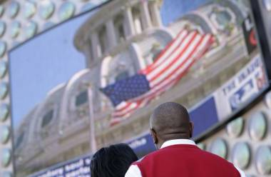 Darren and Valerie Calhoun from Memphis, Tenn. watch the JumboTron outside Planet Hollywood during President Barack Obama's inauguration Tuesday morning on the Las Vegas Strip.