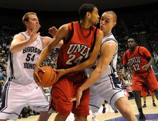 Rene Rougeau looks for the open man as the BYU defense swarms him on Wednesday as UNLV took on BYU at the Marriott Center in Provo, Utah. The Rebels defeated the Cougars 76-70.