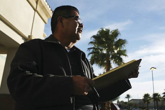 Gilberto Guereque of the Culinary Union seeks signatures Monday outside a grocery for a petition aimed at stopping the city hall project.