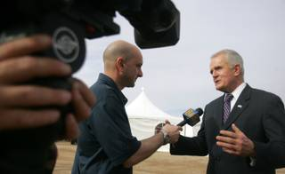 Edward Lawrence, left, of Channel 8 News interviews Gov. Jim Gibbons about renewable energy during the dedication ceremony for Sempra Energy's new El Dorado Energy Solar facility January 22.
